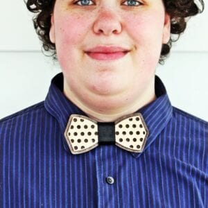 person wearing blue shirt with polka dot wooden bow tie closeup - yarrow